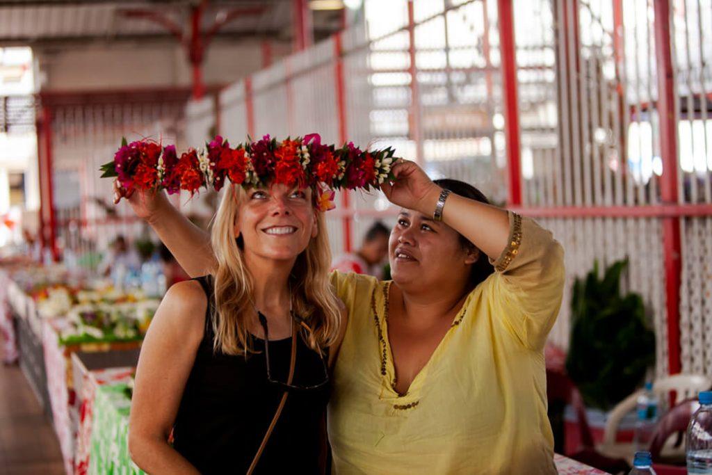 Woman at market putting flower headband on Cathryn